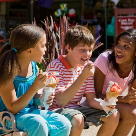 Two girls and a boy eating icecream on a bench