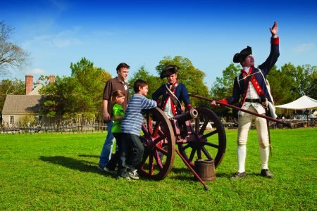 Two men dressed in Colonial attire demonstrate the cannons for two kids with their dadCannon And Kids1